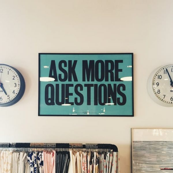 Photo of a wall with a framed poster with the words ask more questions in black capitals against a green background. On the left and the right of the poster are half cropped wall clocks. Below a rack of different coloured skirts