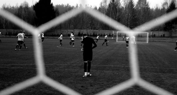 Photo of players on a pitch. Taken from behind one of the goals, up close through the goal net, with the goalkeeper in the immediate foreground looking down at his feet and the other players further up the pitch.