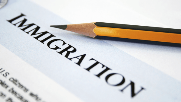 Photo of a cropped page with Immigration in capitals being the only word in clear focus printed on a diagonal with a HB yellow and black striped pencil above it.