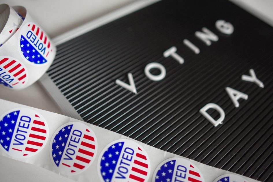 A roll of Stars & Banners Voted stickers slightly unfurledon a partially obscured Voting Day board