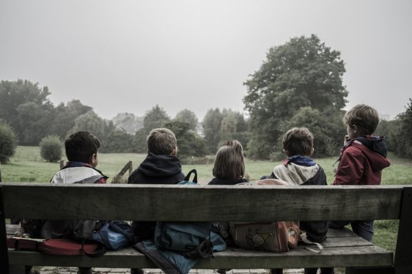 5 kids sat on a park bench looking into the tree-lined distance