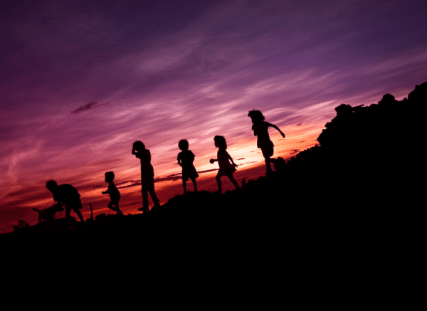 Silhouette of 6 boys and girls with a dog running on a hill as the sun sets