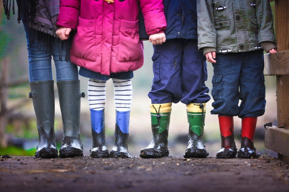4 kids in outdoor clothes and wellies cropped from the chest down