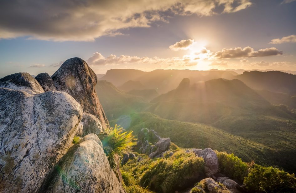 Gray stone formation overlooking green hills during sunrise