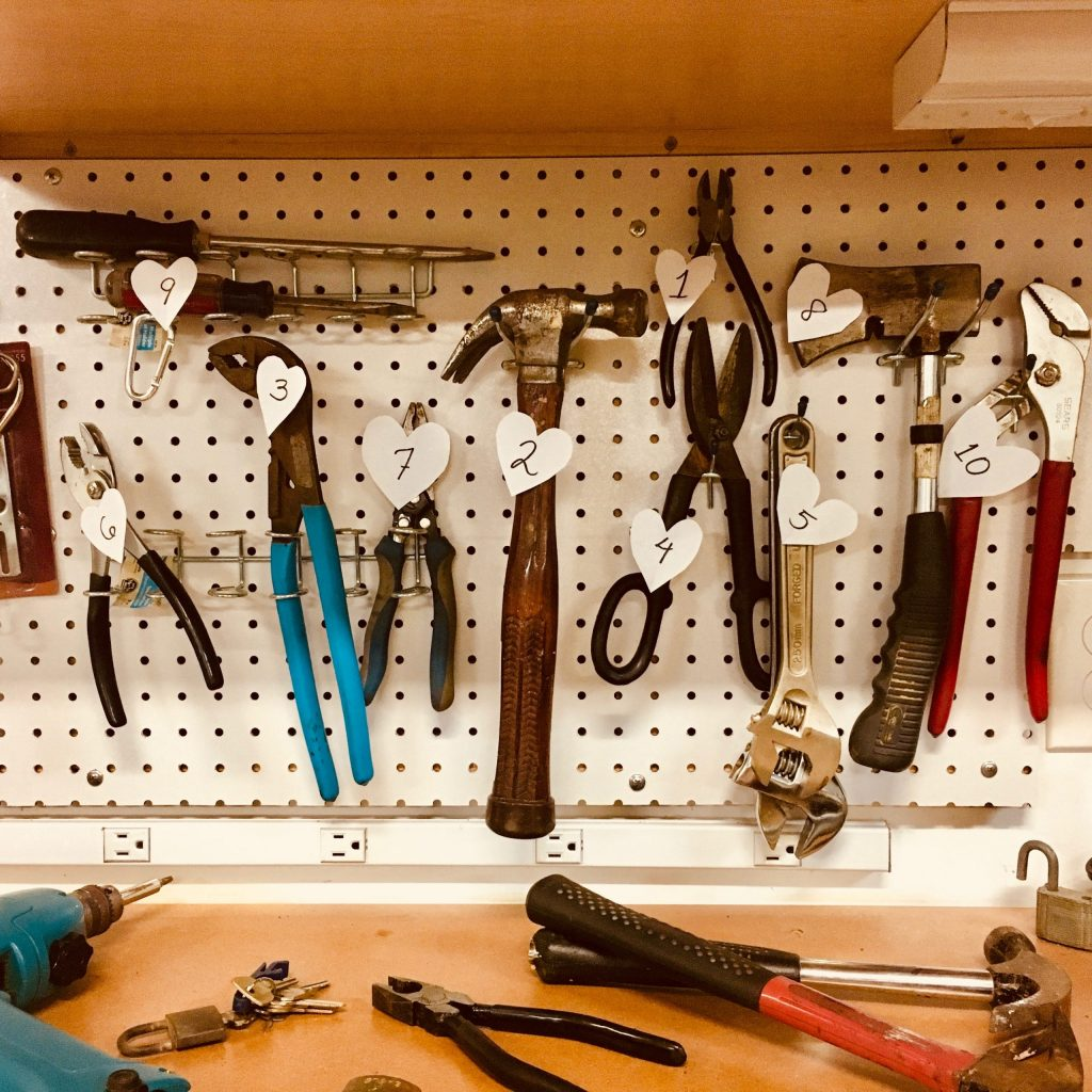 Set of tools, labelled with heart-shaped numbers, hanging on wall brackets