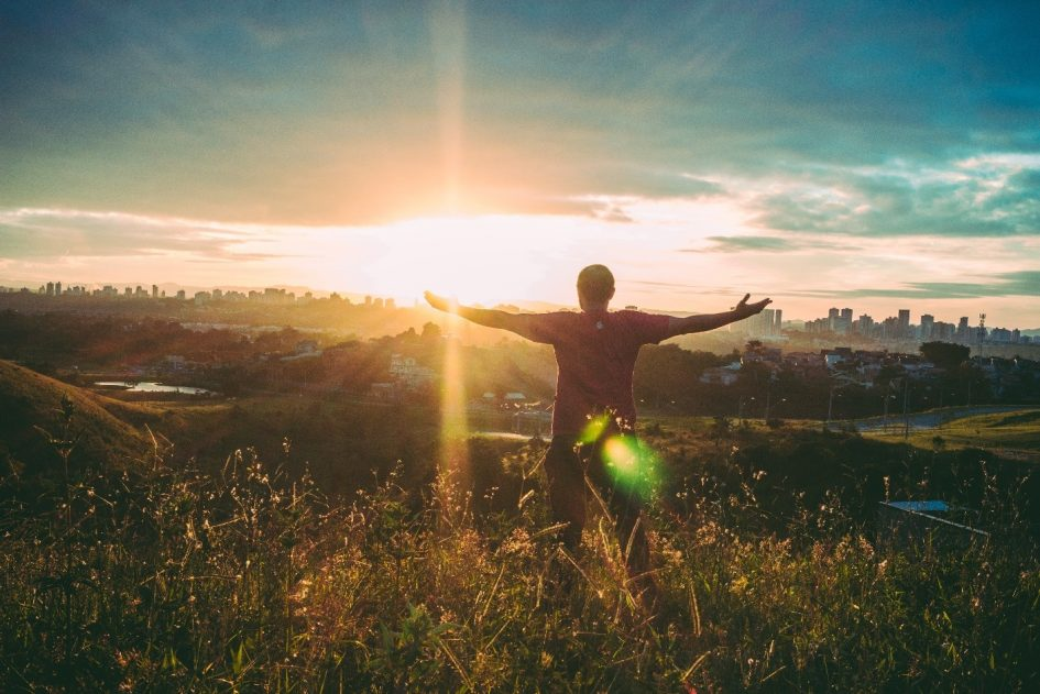 Man on a hill with arms outstretched, welcoming a bright sunrise: a new dawn.